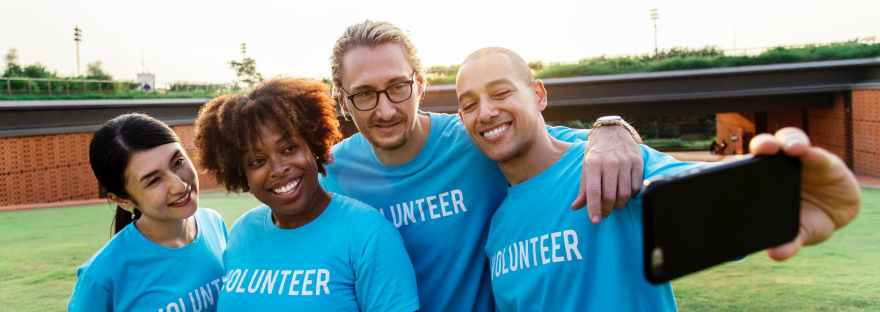 four person taking selfie while wearing blue volunteer t shirt